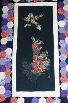 Sois muchas a las que os encanta la cultura japonesa. Lo cierto es que es apasionante en lo que a su mundo estético se refiere, muy alejada del mundo occidental, particular, misteriosa y profunda. Por eso, las labores que cojugan el patchwork con la iconografía japonesa dan un resultado espectacular. Ya os enseñamos esta colcha Kokeshi que a muchas os ha fascinado. En esta ocasión, es una colcha que incluye un panel japonés y que ha realizado Maite. Una geisha y las flores de cerezo…