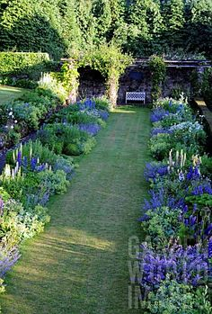 LOOKING ALONG THE RESTORED DOUBLE HERBACEOUS BORDER IN THE GARDEN AT HIGH GLANAU MANOR. THE GARDEN WAS LAID OUT BY H. AVRAY TIPPING IN THE 1920S.
