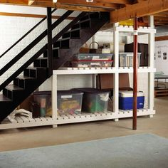 Pack In Supplies. Large, deep shelves running beneath these basement stairs are ideal for stacking bins and boxes. The slatted shelves keep items off the basement floor and out of harm's way should the basement flood.