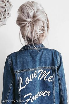 """A denim jacket featuring a """"Love Me Forever"""" embroidered back graphic, buttoned-down front, basic collar, two front flap pockets, two front slit pockets, a frayed hem, and long sleeves."""