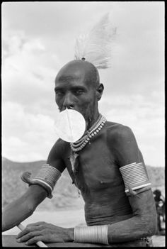 Africa | Portrait of a Turkana elder wearing a feather headdress, large metal nose ornament, and beaded and metal jewellery around his neck and arms. | Kenya; 1961 | ©Wilfred Patrick Thesiger
