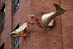 A huge metal salmon seemingly breaks through the corner bricks of the building high above the ground at the South Park Seafood Grill & Wine Bar, Portland OR