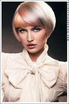 Hair Style: This conservative hairstyle is chic and classy. The style is short all around with a full fringe at the forehead. At the forehead, more hair is styled over at the front on one side. Using a rounded brush, can keep the hair looking neat and tidy.  Hair Cut: This chic, short haircut is clean and stylish.  Hair Colour: The hair colouring is blonde with several different coloured highlights. A touch of pink, a touch of gray and a touch of orange add to this stylish look.