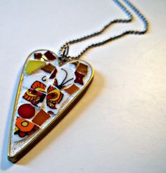 Bronze heart shaped pendant with red, yellow and orange stained glass and broken china.  Appropriate for any age from pre-teen to grandmother.  Comes with a necklace. Pendant is wrapped in tissue paper and placed in an organza bag perfect for gift giving.  Pendant measures 2 x 1 inches.