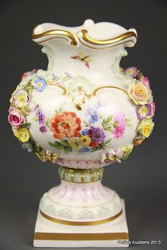 A MEISSEN VASE <br> Circa early 20th century <br> An ovoid urn upon a square base with a gilt scrolled rim, daintily decorated with gilt highlights, and painted and applied garlands of roses, forget-me nots, cornflowers and flying insects, marks for 1818-1924 underside <br> Height: 15cm