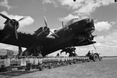 A bomb train, loaded with Small Bomb Containers (SBCs) filled with 4-lb incendiaries, arrives in front of Short Stirling Mark I 'HA-T' of No. 218 Squadron RAF at Marham, Norfolk, in preparation for a raid on Emden, Germany.