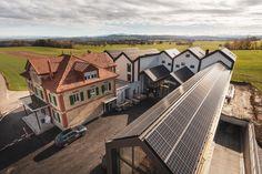 Solarenergie ein wichtiger Teil unserer Nachhaltigkeit-Strategie Auf den markanten Spitzdächern des Neubaus sind hocheffiziente Solarenergie-Panels montiert. Diese bedecken eine Fläche von 620 m2 und liefern eine Maximalleistung von 117 kWp. Pro Jahr kann die Photovoltaikanlage mehr als 108'000 kWh Strom produzieren – genug für rund 25 Haushalte. Wir nutzten die selbst produzierte Solarenergie hocheffizient, speichern Überschüsse und wir werden die Energieeffizienz immer weiter optimieren… Solar, Cocktails, Mansions, House Styles, Home Decor, Households, New Construction, Sustainability, Round Round