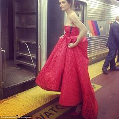 Stopping traffic: Katie Holmes looked like she stepped out of a fashion magazine, wearing a breathtaking crimson colored textured ball gown to New York City's Penn Station on Thursday