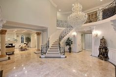 Traditional Entryway with Balcony, Crown molding, complex granite tile floors, Chandelier, Wainscoting, High ceiling