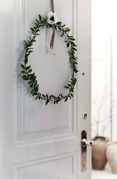 Elegant minimalist wreath for your Scandinavian Christmas decor. Made with olive branches and a white French anemone.