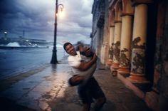 Alex Webb CUBA. Havana. 2002. Playing along the Malecon beneath a storm sky at dusk.