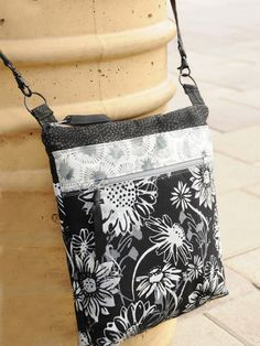 """This stylish bag is great for traveling to quilt shows and on vacations! This fat quarter friendly bag has a long cross-body strap, easy zipper top closure and lots of pockets! It has a total of 6 pockets: 4 outside (including 1 zippered cell phone pocket), and 2 inside. Finished size is 10 1/2""""W x 10""""L x 2""""D using 8 fat quarters or yardage."""