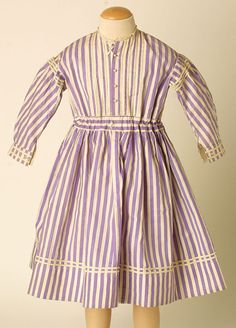 Mauve and white striped cotton dress, 1860-70, at the Manchester City Galleries. Length: 70 cm, Waist: 60 cm, Circumference (hem): 185 cm.