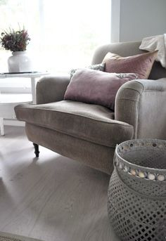 Reading nook, grey sofa and soft pink embellished pillows.