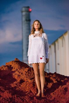 Anna Ewers poses outdoors in a high neckline white dress with long sleeves and hearts for Stern Mode Magazine 2016 issue