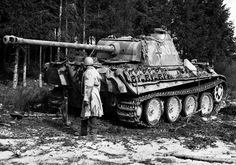 "A US GI examines the hulk of an abandoned German Panther tank (PzKpfw V Ausf G) in the Ardennes sector in Belgium after the failed German ""Hail Mary"" offensive of December 1945. This operation was the last large-scale offensive effort of the Third Reich, which resulted in the sacrifice of the last remaining reserves of front-line combat units."