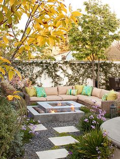A long sectional couch frames a modern double fire pit in this backyard.