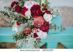 bridal bouquet of pomegranate fruit, peony, pinks and greens lying on a fence turquoise