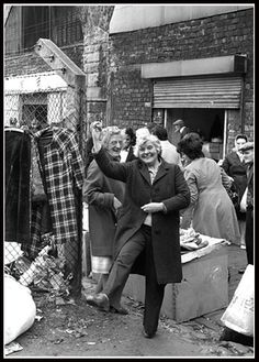 """The quick wit and humour of the Glasgow people is shown in this photograph. I mentioned how people react differently when they spot the camera pointing at them. As you can see, this woman decided to ham it up and demonstrate the Highland Fling. One quick hooch! and the moment was captured.""- D.W. Robertson"