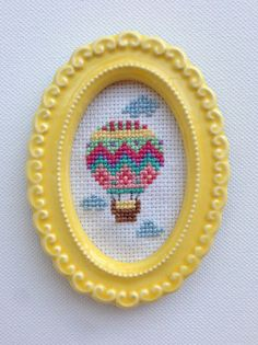 Colorful hot air balloon with clouds completed cross stitch in a small resin frame. --The Deets- This cross stitch features a colorful hot air Tiny Cross Stitch, Simple Cross Stitch, Modern Cross Stitch, Cross Stitch Designs, Easy Cross Stitch Patterns, Cross Stitching, Cross Stitch Embroidery, Embroidery Patterns, Minis