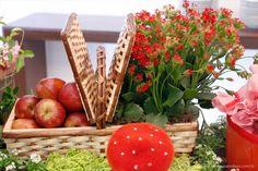 arranjo de flores com cesta de picnic e maçãs para festa chapeuzinho vermelho.