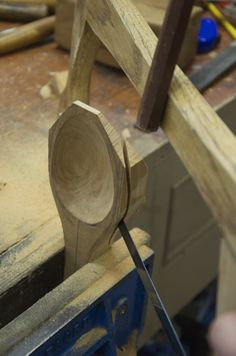 Using a bowsaw to shape a cherry wooden spoon.