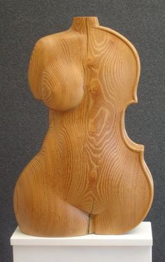 wooden sculpture  This sculpture represents women and music. The associated body part is the hip and a woman is a perfect representation of this. Music can also be both enjoyable and tranquil.