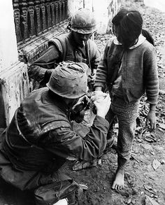 Two U.S. Marines apply bandages to the hand of a Vietnamese girl who was wounded during street fighting in Hue, South Vietnam, February 11, 1968