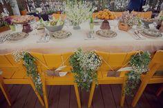 Lindos arranjos em cada uma das cadeiras. Composição perfeita do forte amarelo com a suavidade da decoração sobre a mesa.   Foto: L'amourgraphy  http://www.anoivadebotas.com.br/fernanda-cristiano/