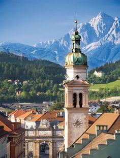 Die Innsbrucker Spitalskirche überragt die pastellfarbenen Häuser der Maria-Theresien-Straße. Von hier schweift der Blick in die Ferne. Tirol als Sehnsuchtslandschaft in den Alpen. (Foto: Innsbruck Tourismus)