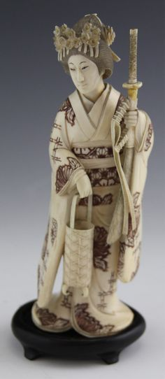 19TH C. MONOCHROME IVORY GEISHA WITH SWORD 19th century monochrome ivory geisha with a sword. Includes a wooden base. The geisha holds the sword in one hand, and a basket in the other. From a private Minnesota collection. Weight: 386g Size: 7""