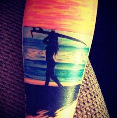 Wonderful looking beach tattoo in silhouette and color. You can see a woman carrying a surf board and walking along the beach in silhouette while behind her is the majestic and colorful sea bathed in sunlight.
