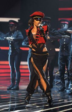 cheryl cole performing on stage in military style cropped red jacket and hat and slashed trousers, work boots