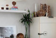 No topo da geladeira em estilo vintage,  ficam grandes vasos de vidro, repletos de rolhas antigas. Para dar graça ao conjunto, a moradora acrescentou um pinguim ao conjunto