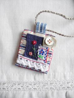 Embroidered flower, ribbons, button, necklace / brooch