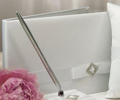 Pure Elegance Wedding Pen Set features a base covered in white satin. It is then decorated with a band of white satin layered with a white satin bow. The bow is decorated with a diamond shaped crystal brooch. White Pen, White Satin, Wedding Guest Book Alternatives, Wedding Ideas, Custom Wedding Cake Toppers, Crystal Brooch, Pen Sets, Classic Elegance, Satin Bows