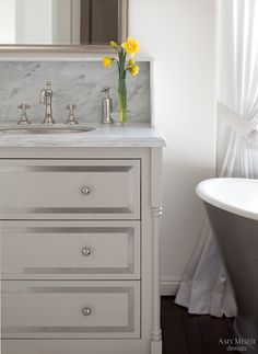 Elegant bathroom with light taupe sink vanity paired with hammered nickel knobs and pewter sink ...