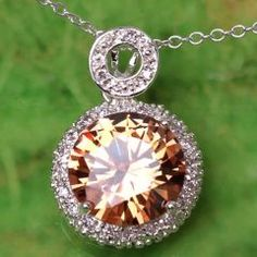 Rainbow topaz pendant with white  topaz accents.  New.  Sterling silver with sterling silver chain.    Deep orange with honey, gold, green and brown highlights sparkle in this over 2 carat stone.  White topaz and sterling silver encircle it to make it shine even more.    Chain included and also sterling silver.  $35