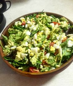 Mixed greens salad with cherry tomatoes, avocado and cheese.