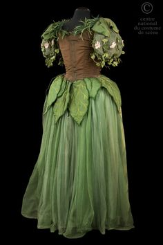 Dance Dress 1954: Une fée. Fantastic costume of medieval style. With Brown faille strapless long dress, trimmed with feathers and leaves in green tulle; sleeves adorned with Ivy and pink flowers. Painted pink and green silk skirt covered with green tulle with panels in silk painted with plant motifs lined iridescent cabochons. Pair of gloves gauntlet green and Brown silk trimmed with green feathers.  Back