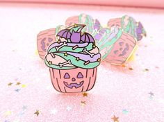 A delicious Halloween cupcake pin to wear during the most spooky time of the year! These are hard enamel pins that are approx 30 mm (1.2 inches). One version in pastel colors and one in more traditional Halloween colors. The finish on both is gold metal and on the back they have two pin posts. The traditional color way comes with purple star backs and the pastel one with yellow star backs. The pin comes on a backing card and will be carefully wrapped when sending it out. Please note that the…
