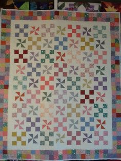 Pinwheel quilt, pieced in 30's fabrics, quilted with daisies and swirls.  Looks great thanks to Marcey's piecing