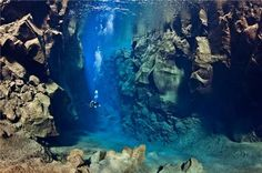 A diver swims between the Eurasian and North American tectonic plates in Silfra Canyon, Thingvellir National Park, Iceland.