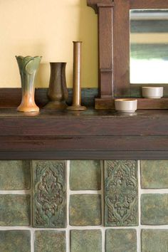 Decorative tiles form the corbel under the mantel shelf in a fireplace surround, by Native Tile.