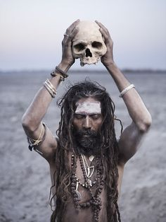 An Aghori man holding a human skull - http://www.cultofweird.com/culture/aghori-cannibal-hindu-monks/