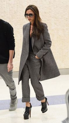 Victoria Beckham wears an extended-hem tweed jacket, cuffed trousers, and stiletto booties