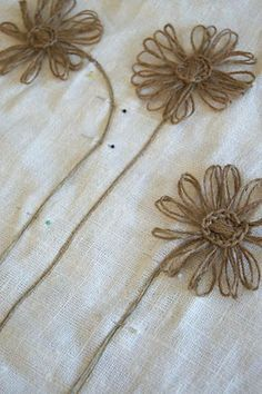 twine flowers- i'm picturing them appliqued around the edge of a tablecloth or on a pillow..Maybe a skirt?