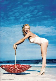 Marilyn Monroe in a white swimsuit at Tobay Beach with a polka dot umbrella, Long Island, Summer 1949.