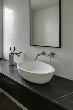 Sleek, modern bathroom with floating sink vanity topped with a soapstone counter which frames an oval vessel sink with polished chrome wall mount faucet over white plastered walls adorned with a floating frame vanity mirror.