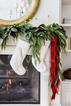 Gorgeous mantel - Christmas greens with red bows and gold mirror hang over the fireplace (My Home Decorated for Christmas. - Pink Peonies by Rach Parcell) Green Christmas, Winter Christmas, All Things Christmas, Christmas Trees, Home For Christmas, Christmas Ornaments, Merry Christmas, Southern Christmas, Christmas Greenery